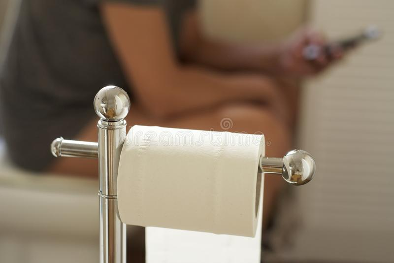 Giovane che utilizza il suo smartphone nella toilette fotografie stock