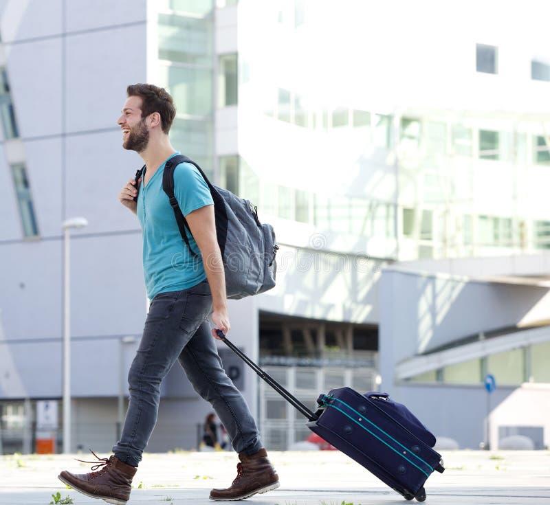 Giovane che viaggia con la valigia e la borsa immagini stock