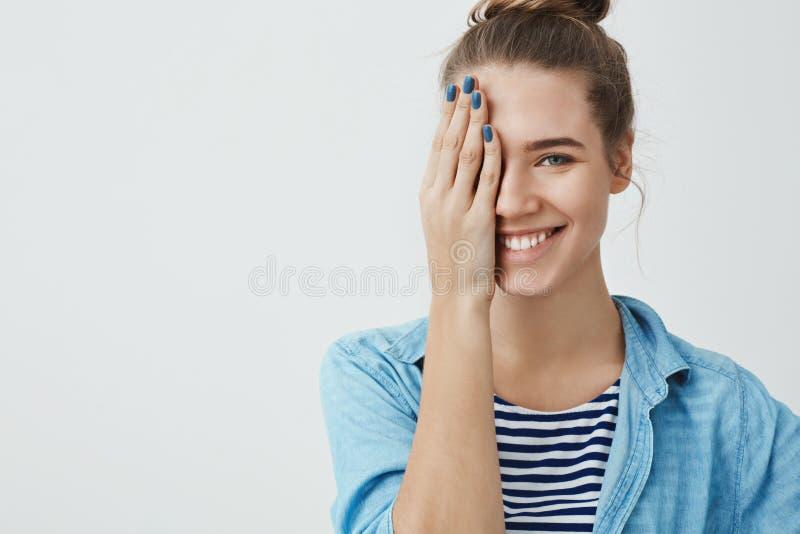 Giovane chiodi fatti casalinga femminile caucasica splendida spensierata entusiasta 25s, coprenti mezzo fronte che sorride franca fotografie stock libere da diritti