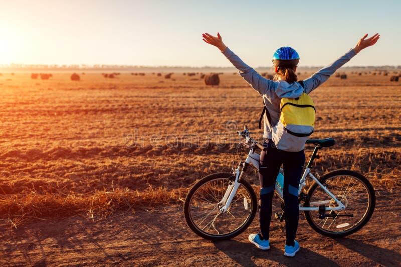 Giovane ciclista felice che alza armi aperte nel campo di autunno che ammira la vista Sentiresi libero della donna fotografia stock libera da diritti