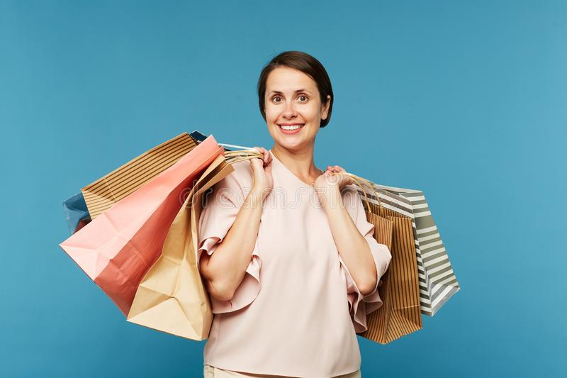 Giovane cliente femminile sorridente grazioso con il mazzo di sacchi di carta fotografia stock