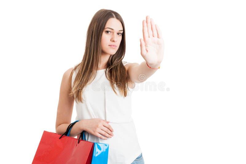 Giovane cliente serio con i sacchetti della spesa che fanno un fanale di arresto immagini stock