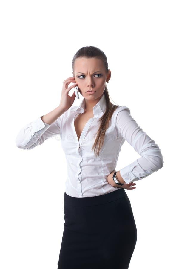 Giovane colloquio serio sexy della donna di affari sul telefono fotografia stock libera da diritti