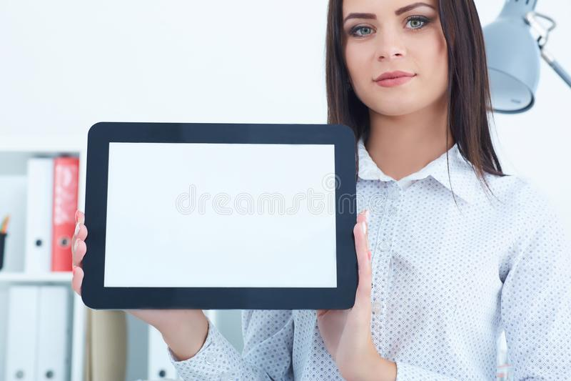 Giovane compressa femminile della tenuta della donna di affari con lo schermo in bianco in mani che si siedono all'ufficio fotografia stock libera da diritti