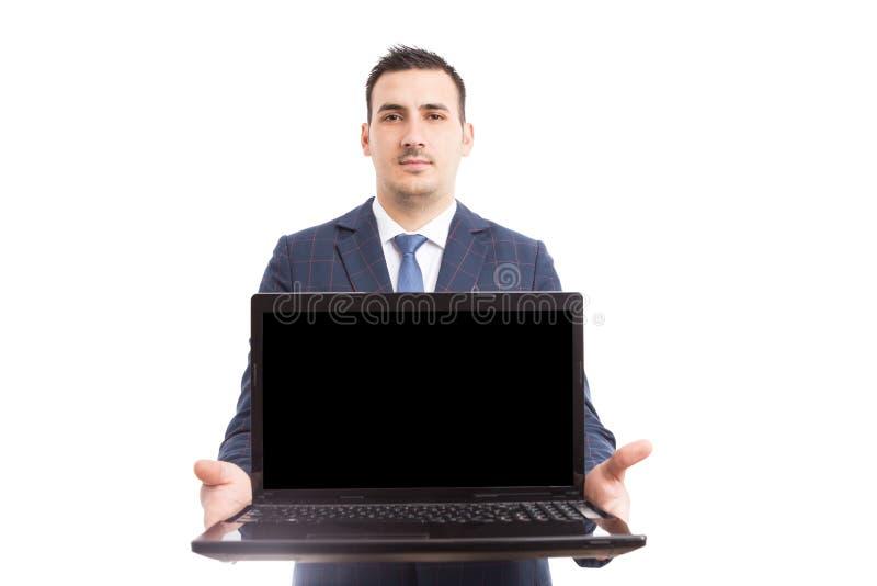 Giovane computer portatile bello della tenuta del mediatore con lo schermo vuoto fotografia stock libera da diritti
