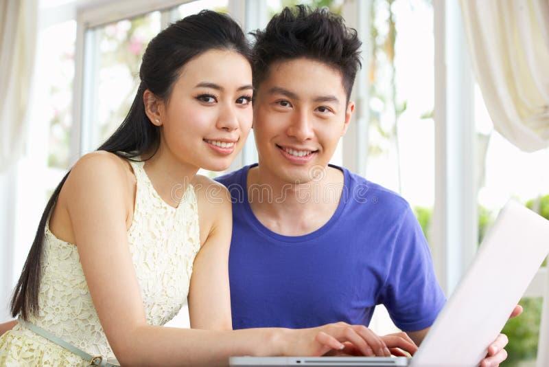Giovane computer portatile cinese usando e delle coppie nel paese fotografia stock libera da diritti