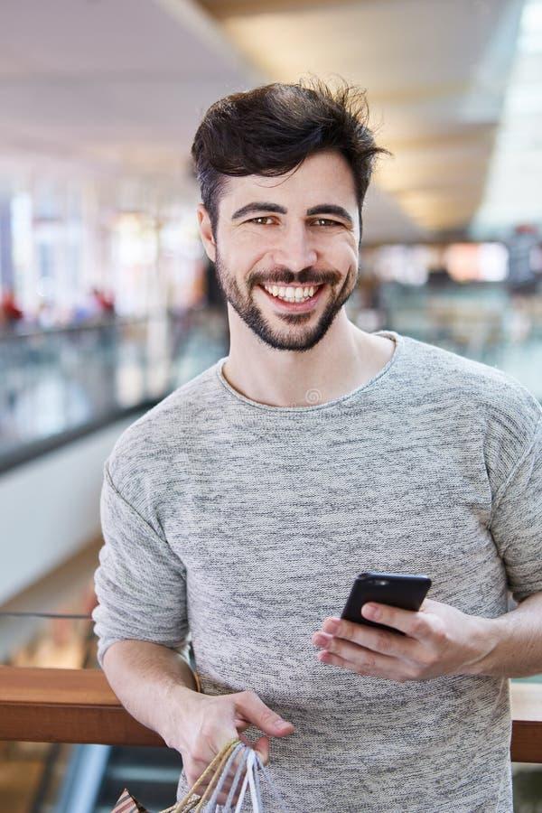 Giovane con acquisto di attimo dello smartphone immagini stock libere da diritti
