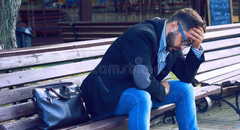 Giovane con espressione facciale triste che si siede su un banco nel parco L'impiegato di concetto ha perso il suo lavoro Dispera fotografia stock libera da diritti