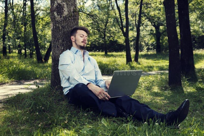 Giovane con funzionamento blu della camicia sul suo computer portatile in un parco pubblico che si siede sulla terra fotografia stock