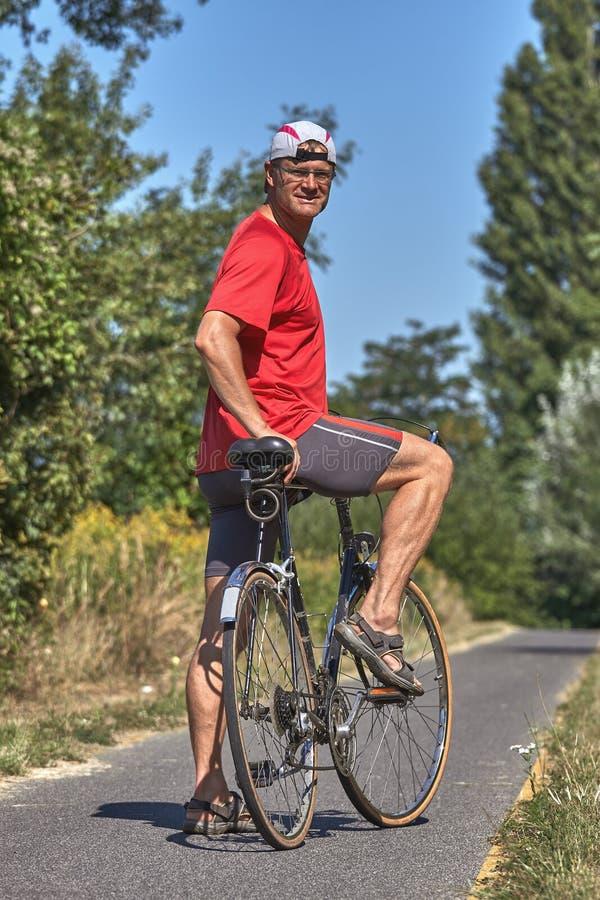 Giovane con gli abiti sportivi rossi sulla strada della bici dall'Ungheria fotografia stock