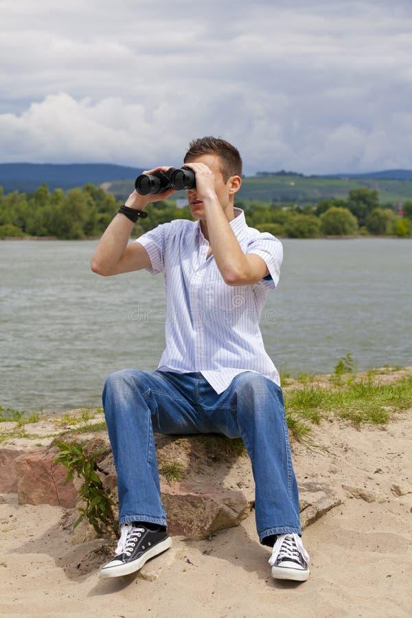 Giovane con il binocolo fotografia stock