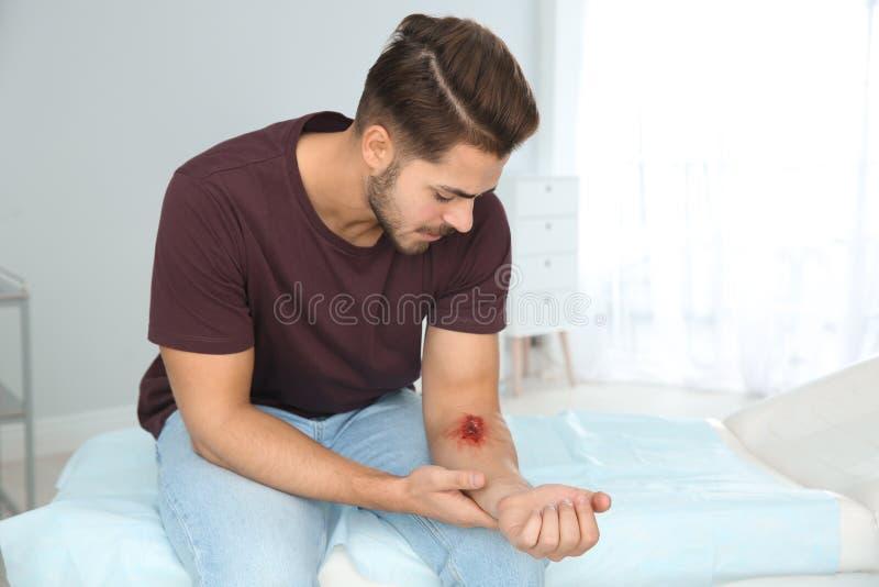 Giovane con il braccio danneggiato in clinica immagine stock