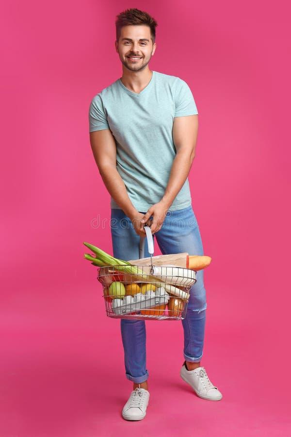 Giovane con il cestino della spesa in pieno su fondo rosa fotografia stock