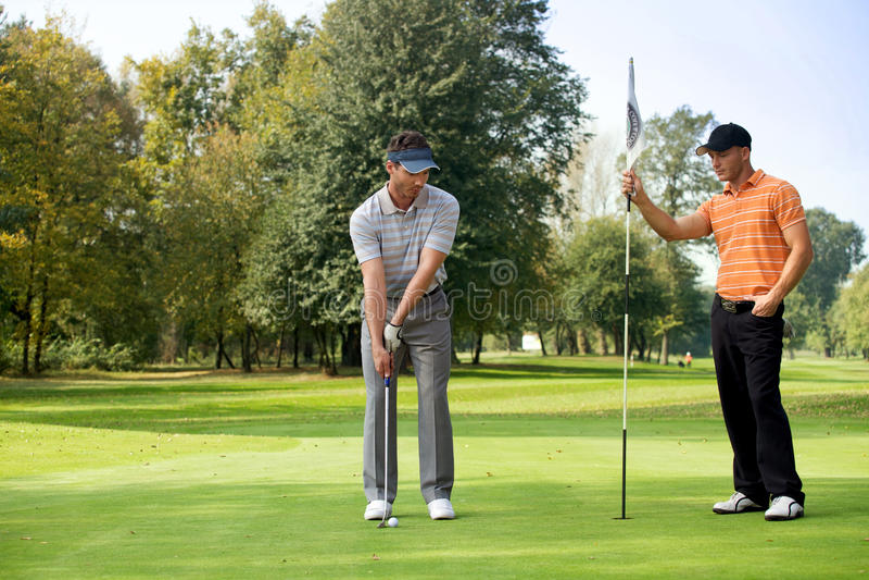 Giovane con il suo amico che gioca golf nel campo da golf immagini stock libere da diritti
