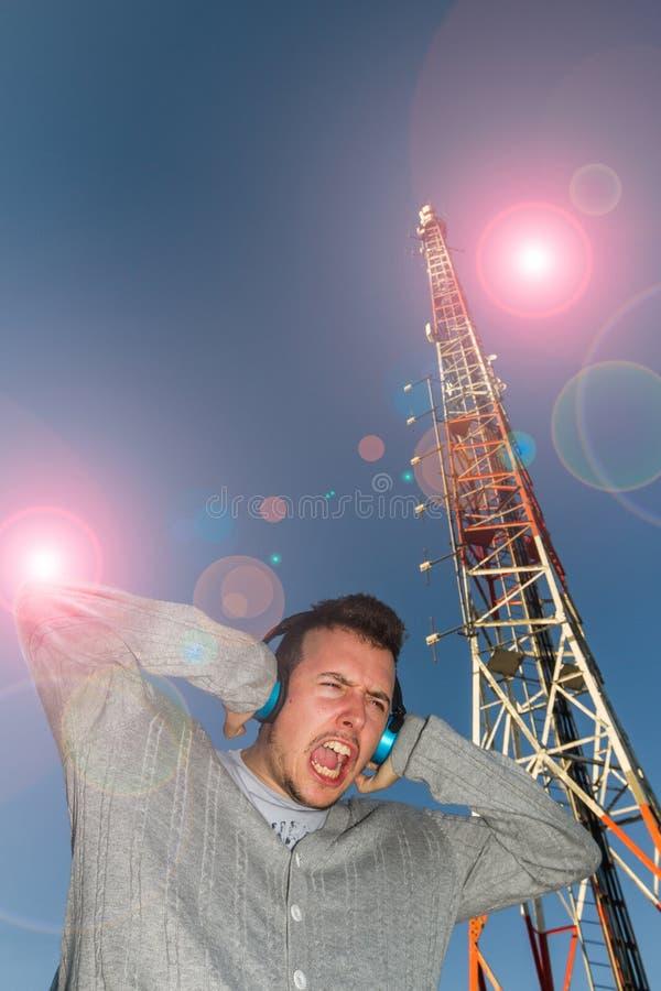 Giovane con l'antenna di telecomunicazioni e dei caschi in mezzo immagine stock libera da diritti