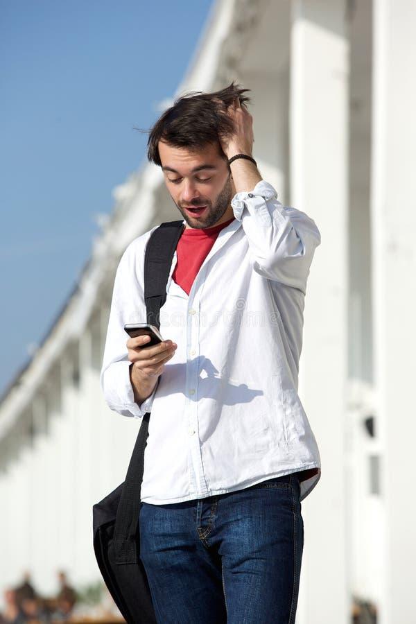 Giovane con l'espressione sorpresa che esamina telefono cellulare fotografia stock