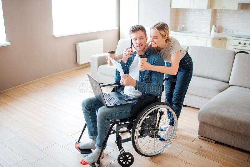 Giovane con l'inabilità che si siede nella sedia a rotelle e nello sguardo indietro Supporto della donna dietro e tenere le tazz fotografia stock
