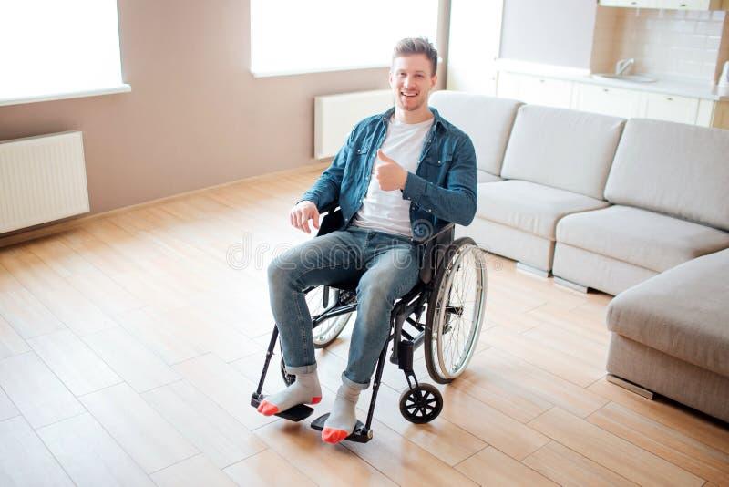 Giovane con l'inabilit? che si siede sulla sedia a rotelle Da solo nella grande stanza vuota Tenendo grande pollice su e sorriso  fotografie stock libere da diritti