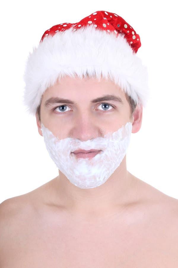Giovane con la rasatura della gomma piuma in cappello della Santa immagine stock libera da diritti