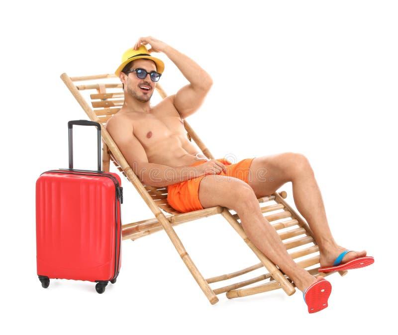 Giovane con la valigia sulla chaise-lounge del sole contro fondo bianco Spiaggia immagini stock
