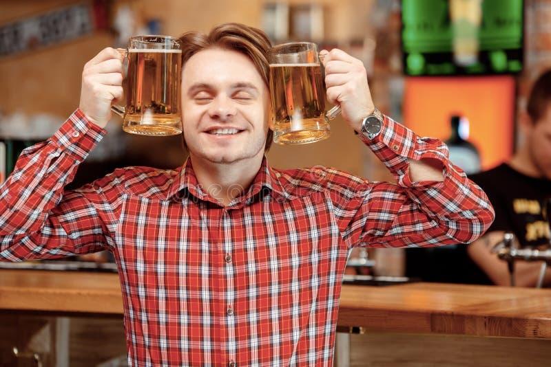 Giovane con le tazze di birra fotografie stock libere da diritti