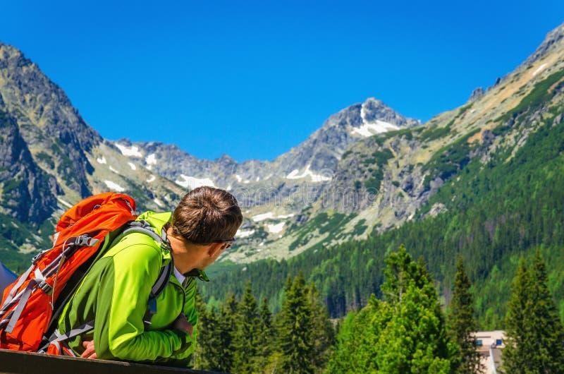 Giovane con lo zaino che esamina i picchi di montagna fotografia stock