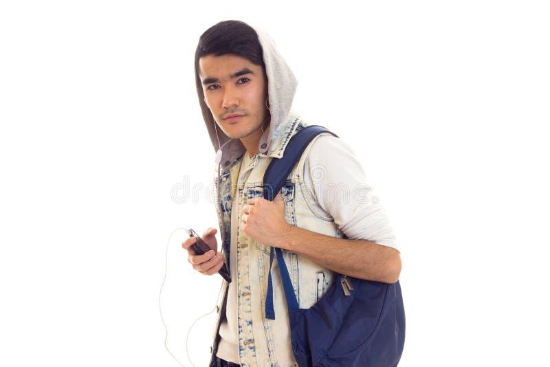 Giovane con lo zaino, lo smartphone e le cuffie immagine stock