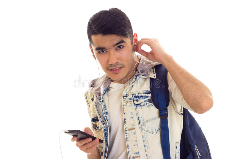 Giovane con lo zaino, lo smartphone e le cuffie fotografia stock
