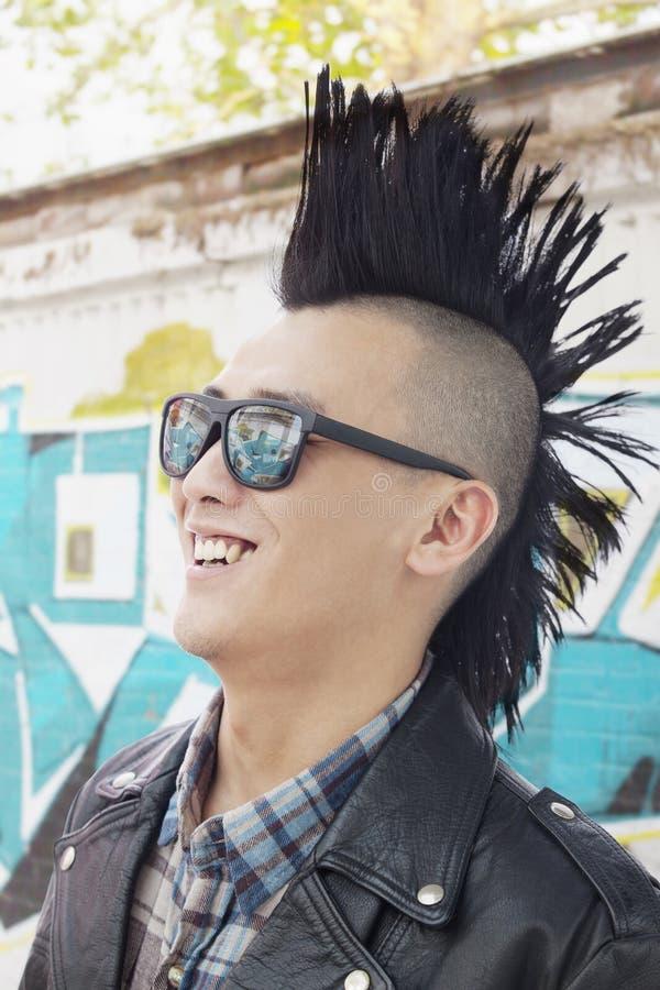 Giovane con sorridere punk degli occhiali da sole e del Mohawk fotografie stock