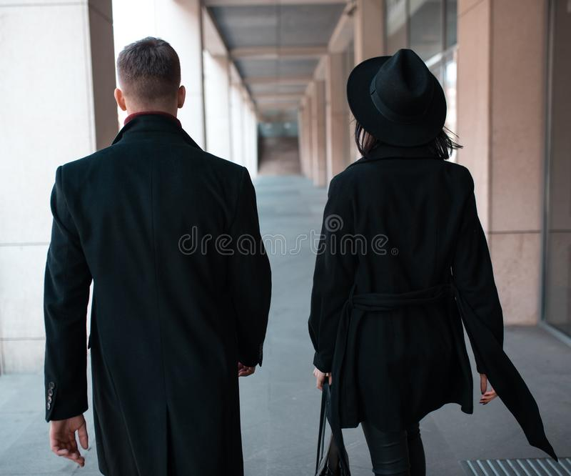 Giovane con un cappotto nero e una giovane donna con un cappello nero e un cappotto nero immagine stock libera da diritti
