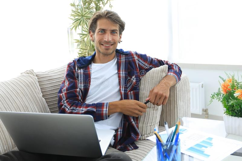 Giovane con un computer portatile che si siede su un sofà vicino ad un tavolino da salotto fotografie stock