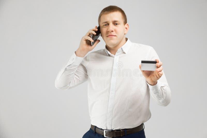 Giovane con una carta assegni ed i supporti del telefono cellulare isolati su fondo leggero fotografia stock libera da diritti
