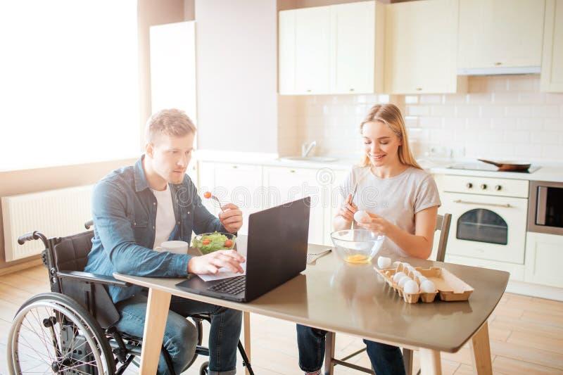 Giovane concentrato su funzionamento della sedia a rotelle con il computer portatile e l'insalata di cibo Studiando con l'inabili fotografie stock
