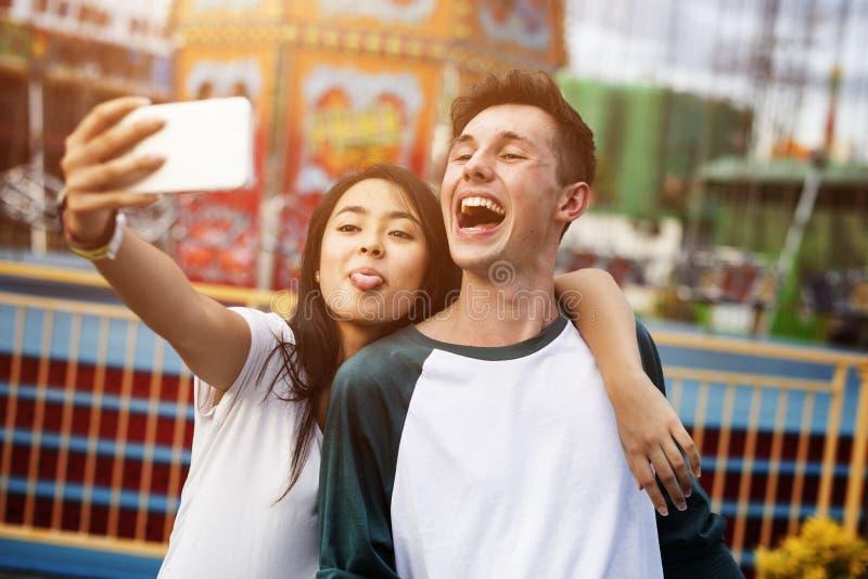 Giovane concetto del parco di divertimenti della data delle coppie immagine stock libera da diritti
