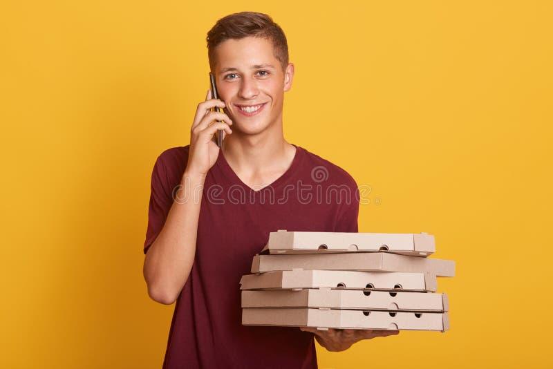 Giovane condizione allegra del ragazzo isolata sopra fondo giallo in studio, tenendo le scatole di cartone con pizza e lo smartph fotografie stock