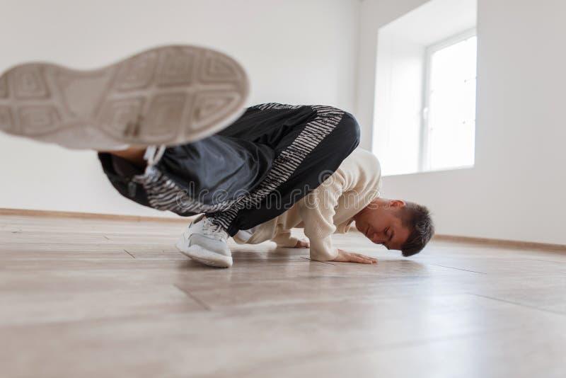 Giovane condizione del ballerino sul braccio Breakdance ballanti dell'uomo immagini stock