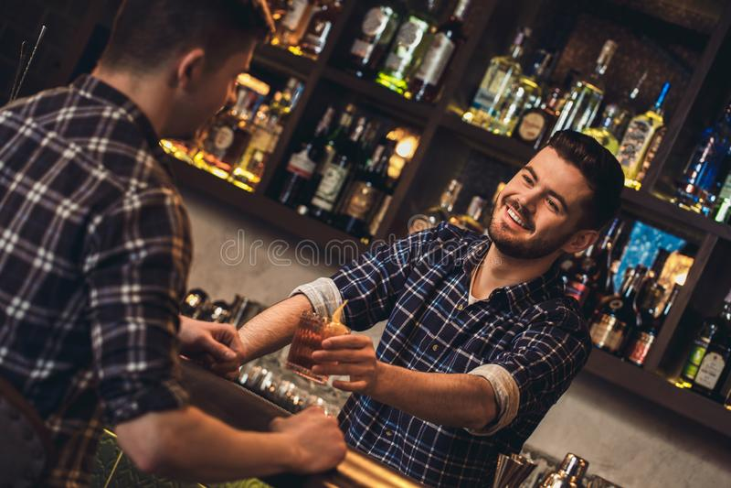 Giovane condizione del barista al contatore della barra che dà il cocktail del cliente allegro fotografia stock
