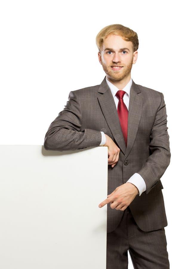 Giovane condizione dell'uomo d'affari mentre con una lavagna in bianco, isola fotografia stock libera da diritti