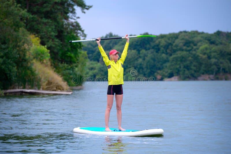 Giovane condizione della ragazza del surfista su un bordo con una pagaia alzata su su un fondo degli alberi verdi immagine stock libera da diritti