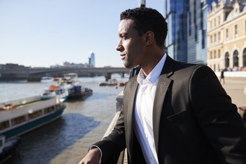 Giovane condizione posteriore dell'uomo d'affari alla riva del fiume di Tamigi nella città di Londra che ammira la vista, fine su immagine stock