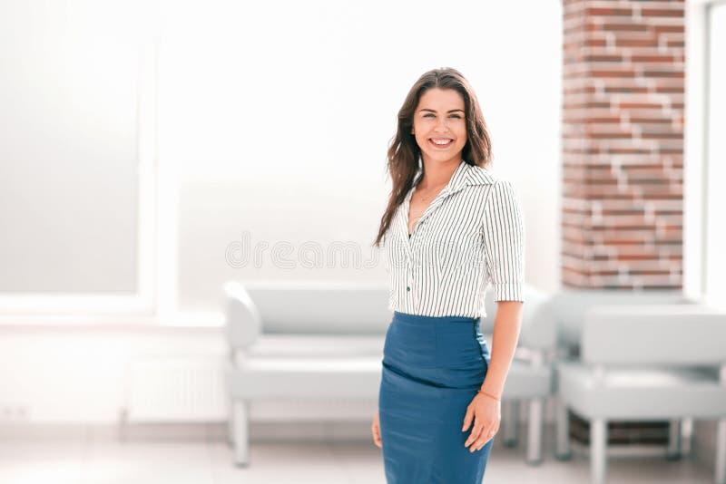 Giovane condizione sorridente della donna di affari nell'ingresso dell'ufficio immagini stock