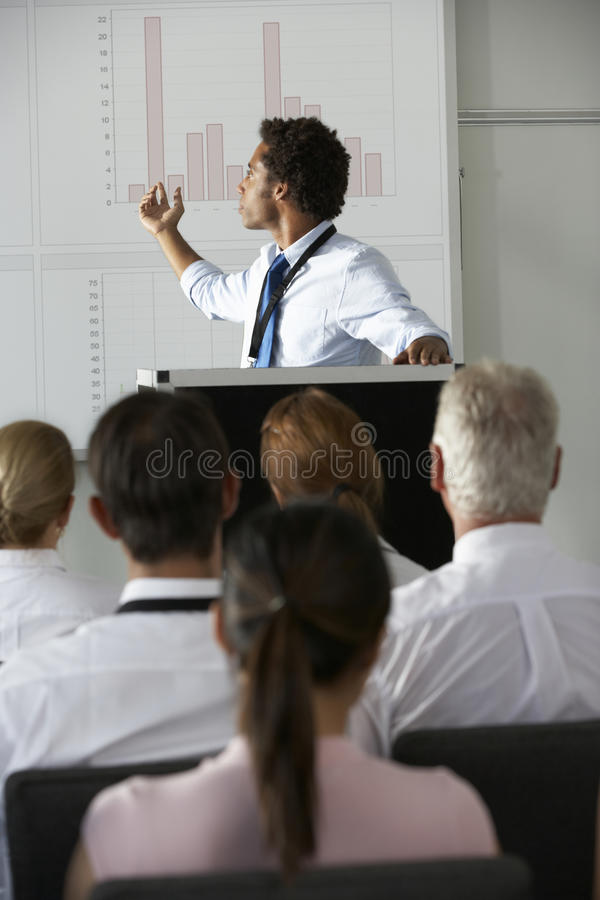 Giovane conferenza di Delivering Presentation At dell'uomo d'affari immagine stock