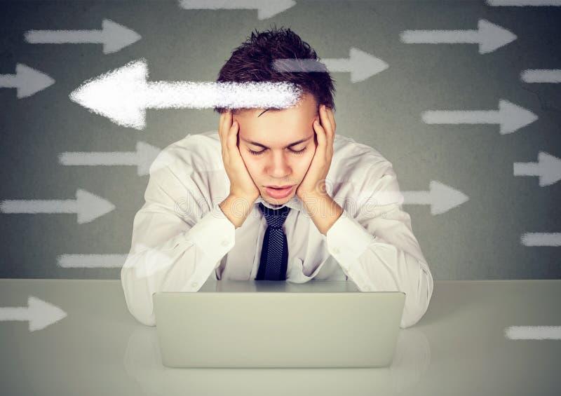 Giovane confuso incerto che si siede davanti al computer portatile immagine stock libera da diritti