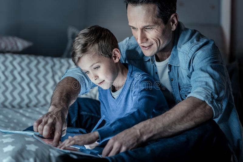 Giovane contentissimo che studia con suo figlio fotografie stock libere da diritti