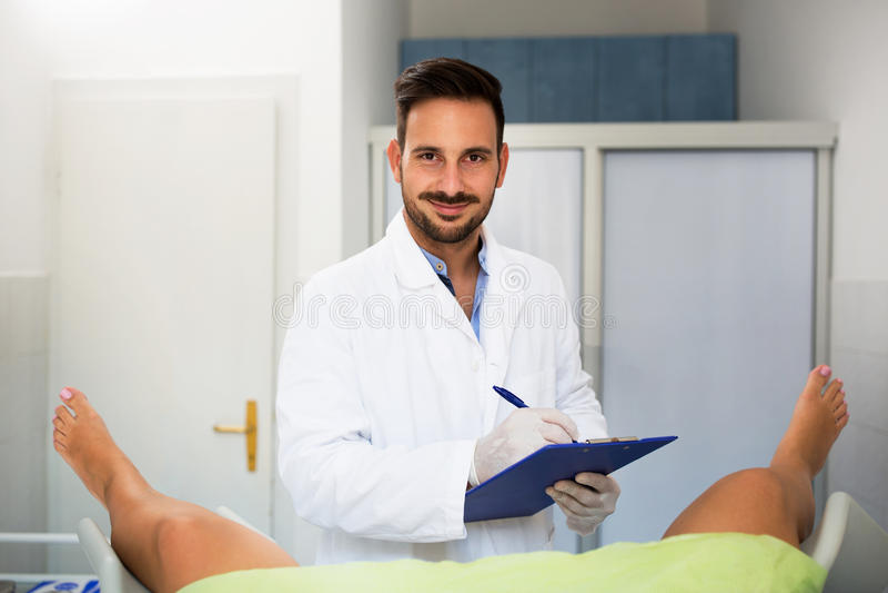 Giovane controllo maschio del ginecologo di medico sul suo paziente immagine stock