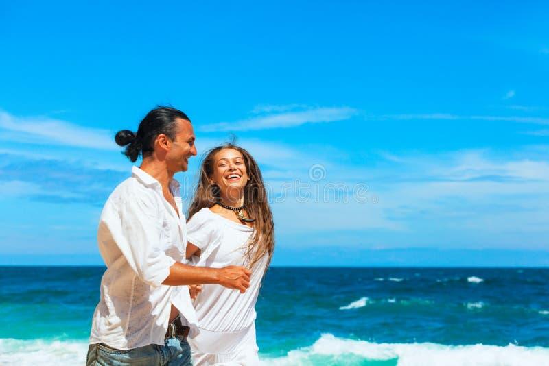 Giovane coppia guidata da una spiaggia di sabbia bianca lungo il mare immagini stock libere da diritti