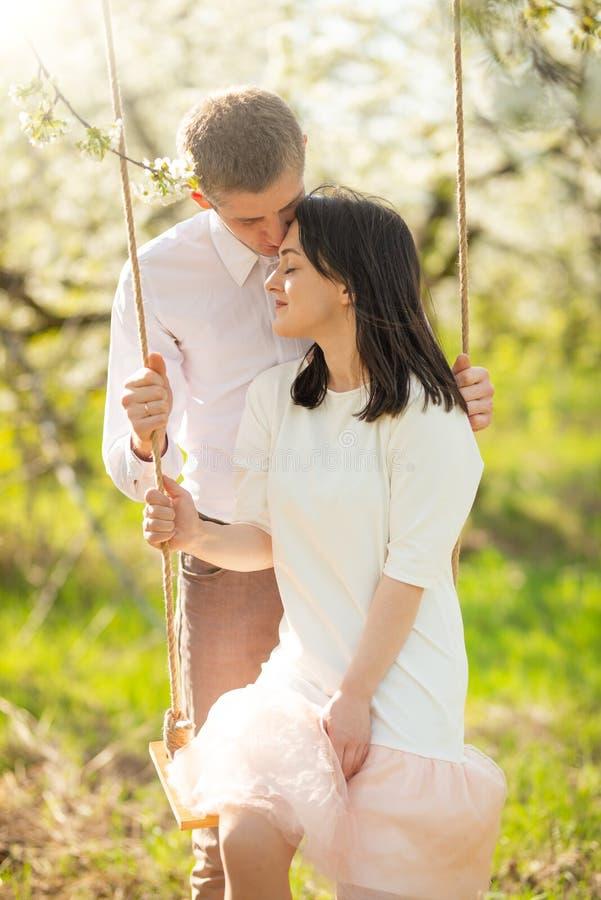 Giovane coppia sposata, su un'oscillazione in un giardino fiorito o in un parco Calorosamente, umore di amore, della primavera e  fotografia stock libera da diritti
