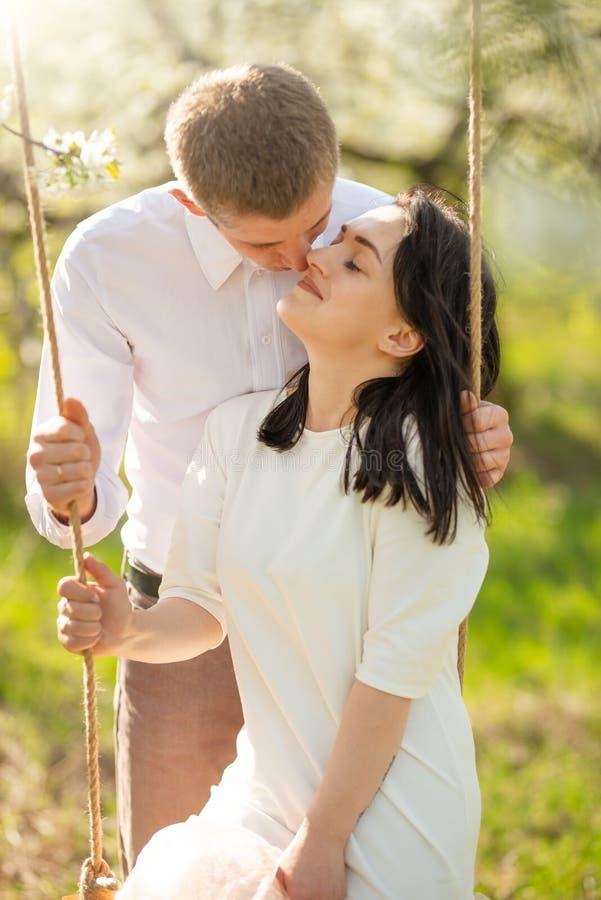 Giovane coppia sposata, su un'oscillazione in un giardino fiorito o in un parco Calorosamente, umore di amore, della primavera e  fotografia stock