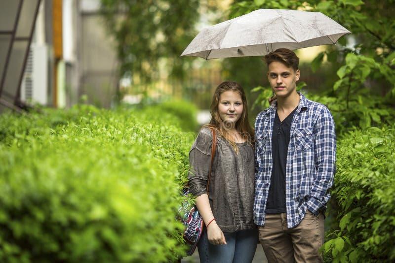 Giovane coppie, ragazzo e ragazza stanti sotto un ombrello sulla pista verde nell'iarda anteriore vicino alla casa fotografia stock