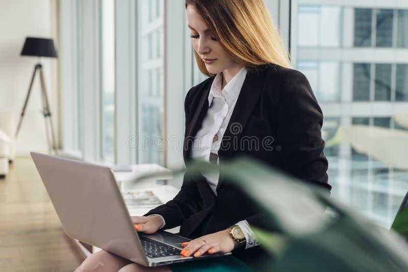 Giovane copywriter femminile che scrive un testo di pubblicità che scrive sulla tastiera del computer portatile che si siede nell fotografia stock libera da diritti
